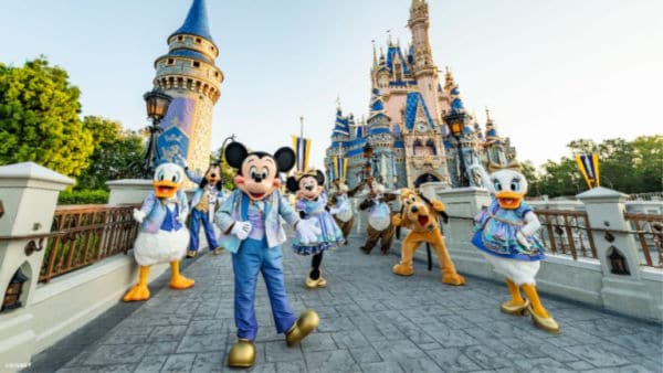 Mickey Mouse and friends in EARidescent costumes in front of Cinderella's Castle
